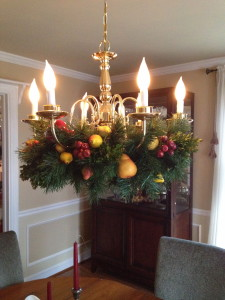 The chadelier get a Christmas makeover with a wreath adorned in fruit.